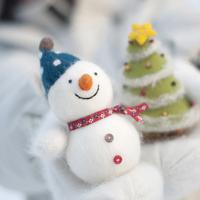 雪だるまとクリスマスツリーを持つ手元