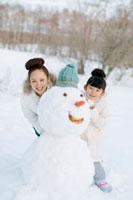 雪だるまと遊ぶ親子