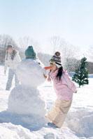 雪だるまと遊ぶ女の子と母親