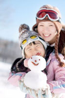 雪だるまを手に持つ親子