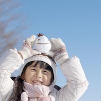雪だるまを頭の上にのせた女の子 20027006597| 写真素材・ストックフォト・画像・イラスト素材|アマナイメージズ