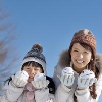 両手に雪だるまを持ち微笑む親子