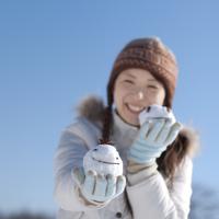 両手に雪だるまを持ち微笑む女性