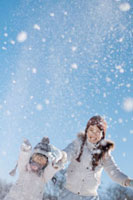 空に雪を舞い上げて遊ぶ親子 20027006606| 写真素材・ストックフォト・画像・イラスト素材|アマナイメージズ