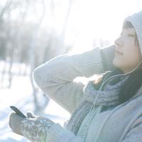 雪原の中で音楽を聴く女の子 20027006667| 写真素材・ストックフォト・画像・イラスト素材|アマナイメージズ