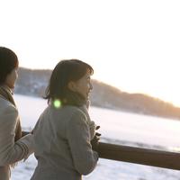 冬の湖を眺める2人のシニア女性