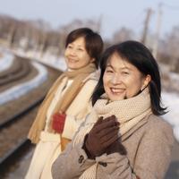 冬の駅のホームに立つ2人のシニア女性