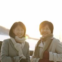 冬の湖と夕日の前で微笑む2人のシニア女性