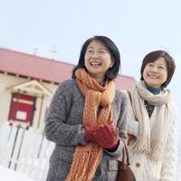 マフラーと手袋をして微笑む2人のシニア女性