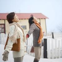 空を見上げて深呼吸する2人のシニア女性