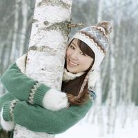 雪景色の中で木の幹に抱きつく20代女性