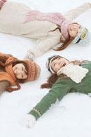 雪の上に寝転ぶ3人の20代女性 20027006688| 写真素材・ストックフォト・画像・イラスト素材|アマナイメージズ