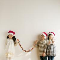 サンタの帽子をかぶりクリスマスグッズを持つ子供たち