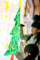 窓にクリスマスツリーのお絵描きをする子供たち