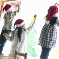 サンタの帽子をかぶり窓にクリスマスのお絵描きをする子供たち