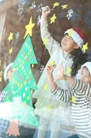 窓にクリスマスツリーのお絵描きをする子供たち 20027006734| 写真素材・ストックフォト・画像・イラスト素材|アマナイメージズ