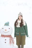 大きな雪だるまと並ぶ20代女性