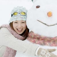 大きな雪だるまに抱きつく20代女性