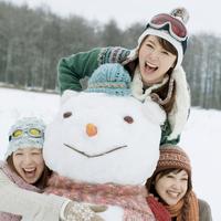 大きな雪だるまに抱きつく3人の20代女性