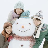 大きな雪だるまで遊ぶ3人の20代女性
