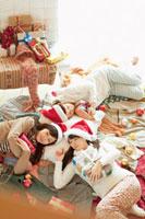 クリスマスパーティーで遊び疲れて洋服の上で眠る20代女性