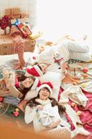 たくさんの服の上でクリスマスプレゼントを抱える20代女性
