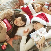 たくさんの服の上でクリスマスプレゼントを抱いて眠る20代女性