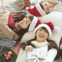 サンタの帽子をかぶりプレゼントを抱く3人の20代女性