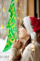 窓に描いたクリスマスツリーに願い事をする20代女性