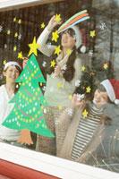 サンタの帽子をかぶり窓にクリスマスツリーの絵を描く20代女性