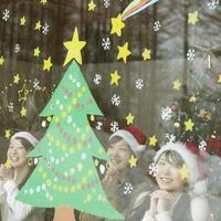 窓に描いたクリスマスツリーに願い事をする20代女性たち