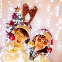 クリスマスのデコレーションとイルミネーションを巻いて光る女性