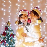 クリスマスのイルミネーションを巻く女性とクリスマスツリー