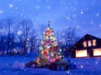 雪の中の光り輝くクリスマスツリーと灯りをともした家