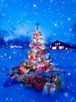 雪の中の光り輝くクリスマスツリーとたくさんのプレゼント