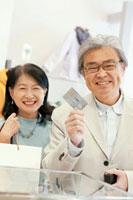 買い物をしてクレジットカードで支払うシニア夫婦