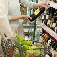 スーパーでワインを選ぶシニア夫婦