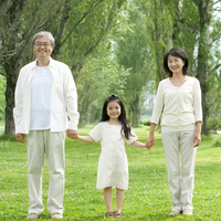 ポプラ並木で手をつなぐシニア夫婦と孫