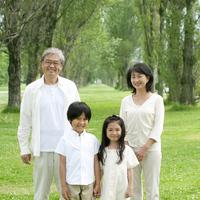 ポプラ並木で微笑むシニア夫婦と孫