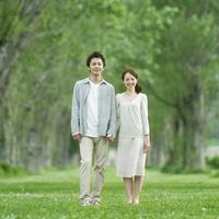 ポプラ並木の前に立つカップル