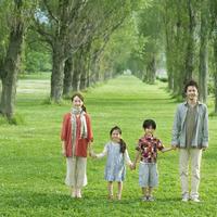 ポプラ並木で手をつなぐ親子