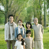ポプラ並木の前で微笑む3世代家族