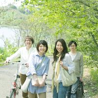 並木道で微笑む4人の大学生たち