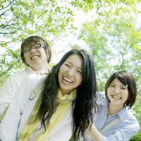 並木道で微笑む3人の大学生たち