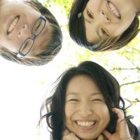 笑顔で覗き込む3人の大学生たち