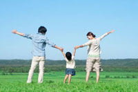 草原で手をつなぐ親子の後姿