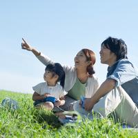 草原に座り空を指差す親子