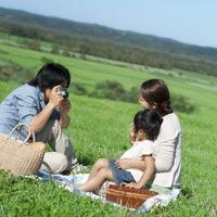 草原に座り子供の写真を撮る親子