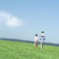 草原で子供を肩車して歩く親子の後姿