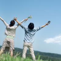 草原で両手を伸ばすカップルの後姿